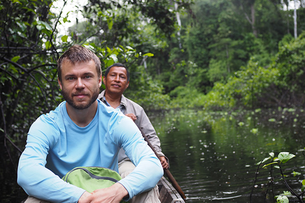John Wilmes inside a canoe on a river in the Amazon rainforest