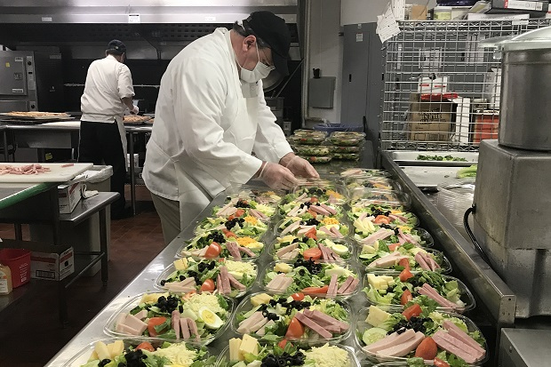 a chef prepares multiple salads in to go containers