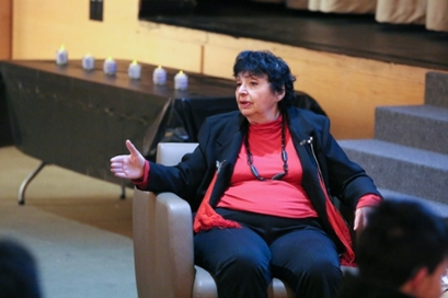 Inge Auerbacher, who survived the Terezin concentration camp as a child, seated in a chair with in a red shirt and black blazer