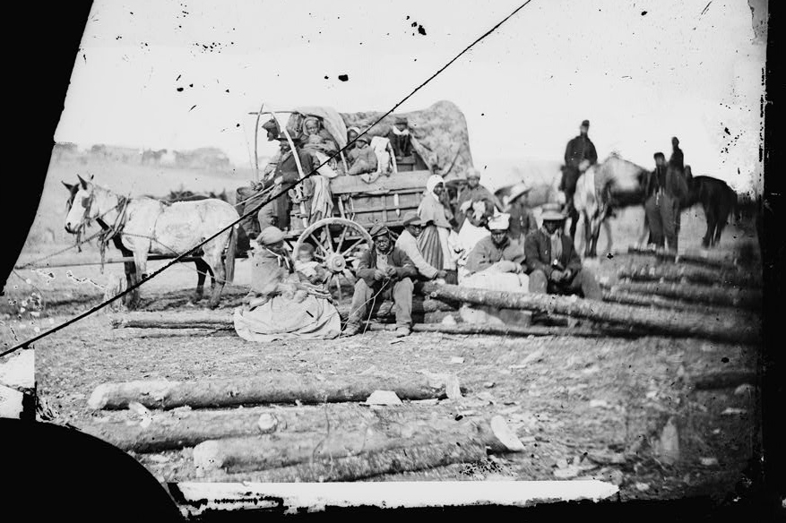 a damaged black and white photo of a group of escaped enslaved people around a covered wagon pulled by horses with sociers in the background