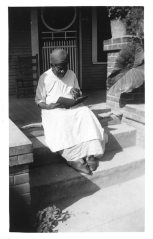 Black and white photo of Mary Armstrong, former slave, sitting on a porch stoop in 1937 with a book in her hand