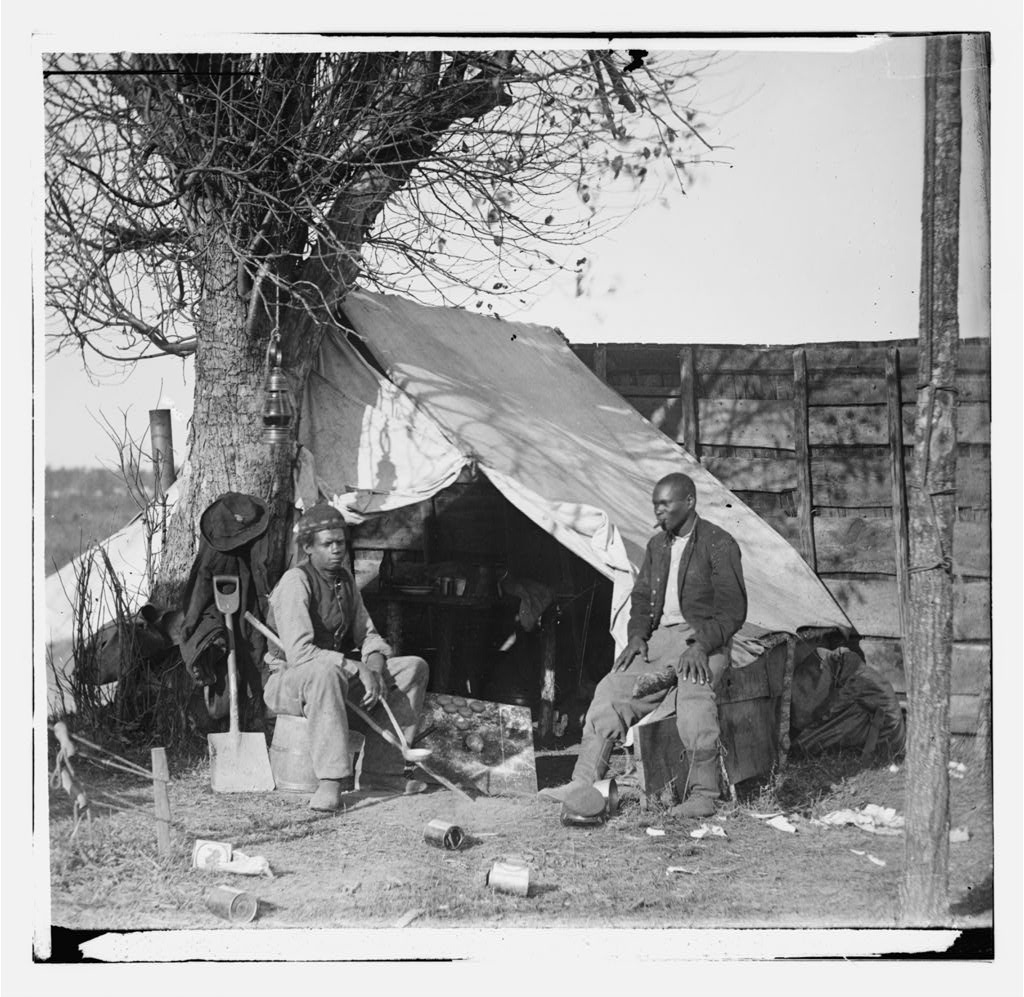 two former slaves sit in front of a tent next to a tree