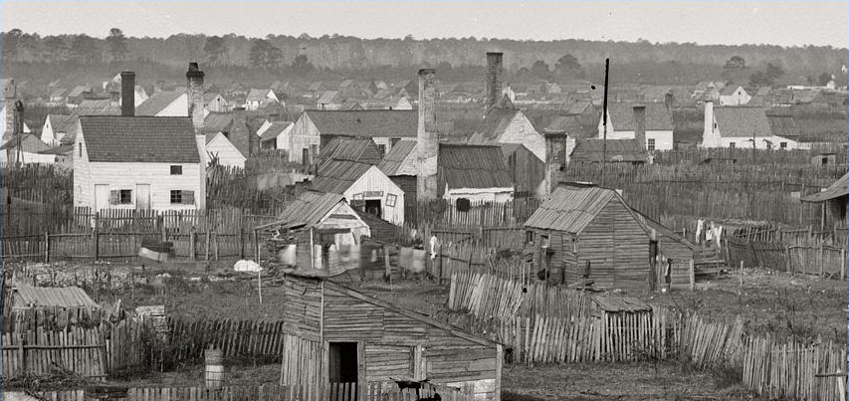 black and white photo of Slabtown, part of a refugee camp for escaped enslaved people during the Civil War. Some painted houses with chimneys and other shacks made of wood divided by slab fences
