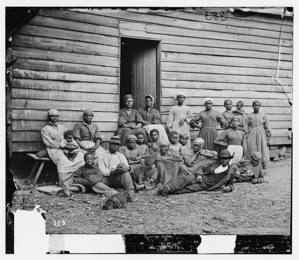 A group of escaped enslaved people in front of a clapboard refugee house in Virginia