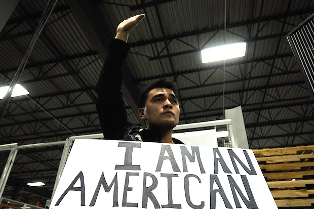 Jose Antonio Vargas holding a sign that says I am an American.