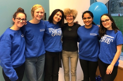 female students in blue Waltham Group t-shirts stand with arms around each other