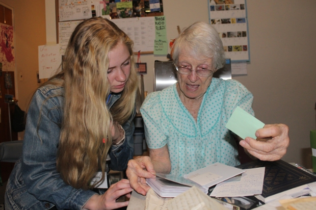 female student with long blond hair and denim jacket looks at letters with elderly woman in nightgown