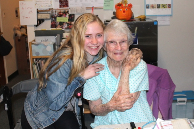 Student with long blond hair and denim jacket hugs elderly soman in nightgown as both look at camera