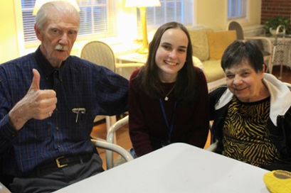 an older man in a blue shirt gives a camera a thumbs up, with his arm around a female student and his wife, an older woman, on the right. All are seated at a table.