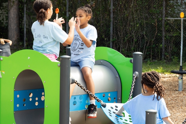 little girls in blue t-shirts play on playground equipment