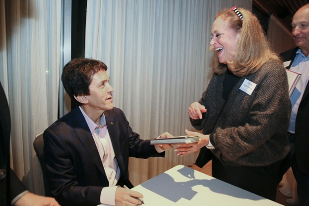 Mitch Albom '79 in a jacket seated at a table, hands a book to a smiling woman with long hair.