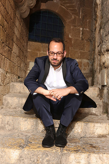 composer Yair Klartag in a suit with open shirt collar sits on a step in a stone stairway