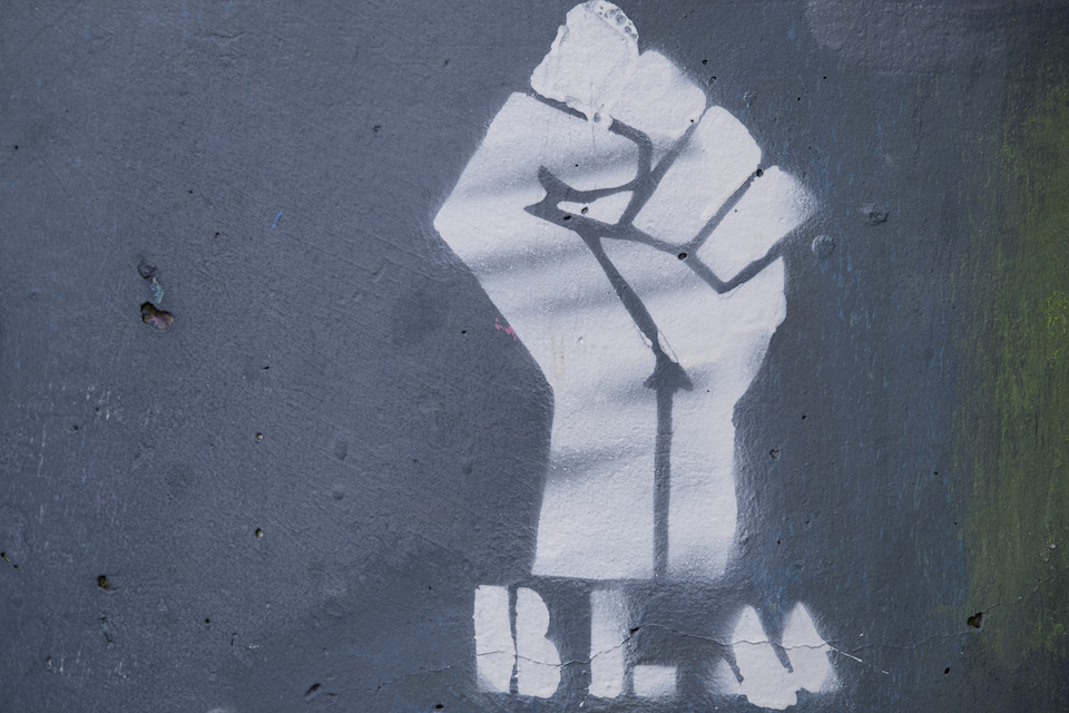 A spray painted raised fist with BLM underneath on concrete
