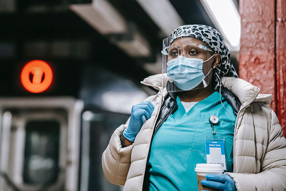 A nurse waits for a subway train.
