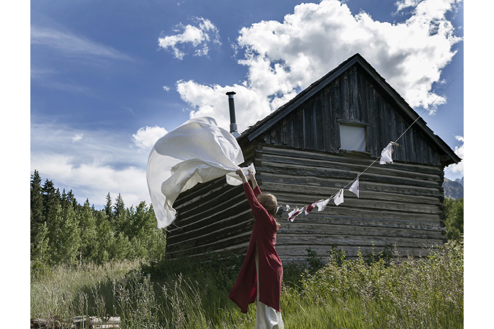 woman shaking white cloth out to dry
