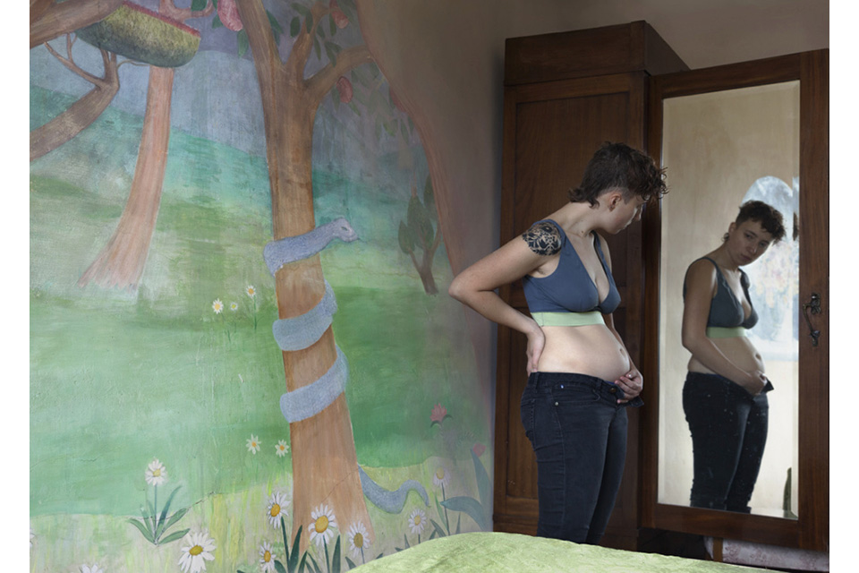 woman looking in the mirror, sticking her stomach out and holding it