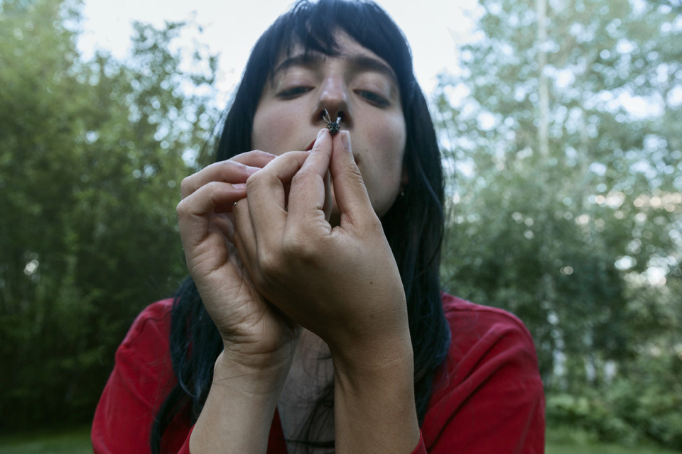 close up image of woman inspecting an insect