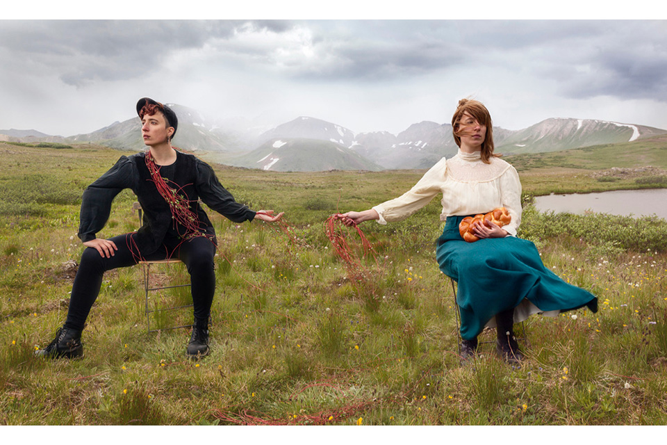 two women (Shterna Goldbloom) dressed differently holding hands in a field