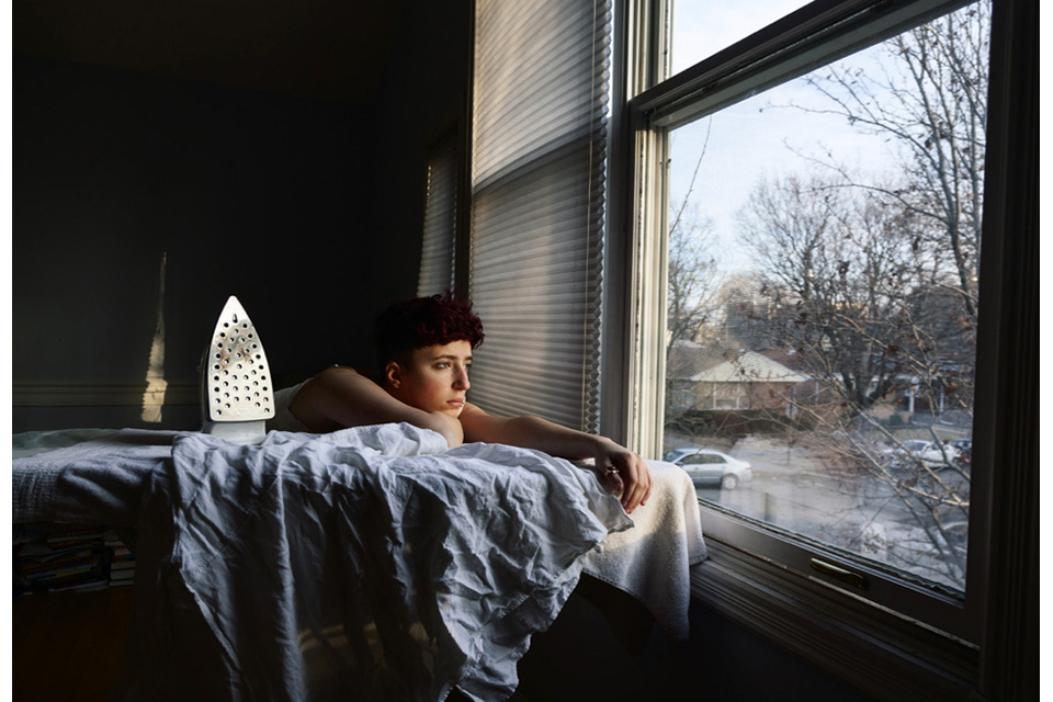 young woman leaning on ironing board, looking out the window